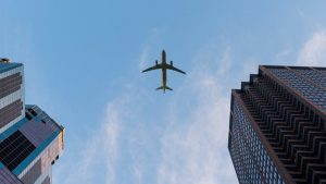 airplane in the sky flying over buildings