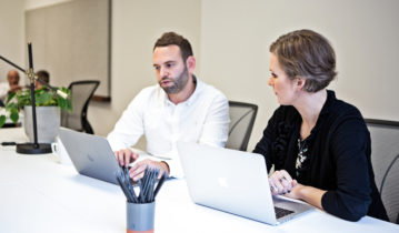 two colleagues working with laptops