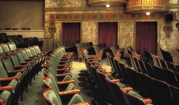 Old theatre with empty green chairs